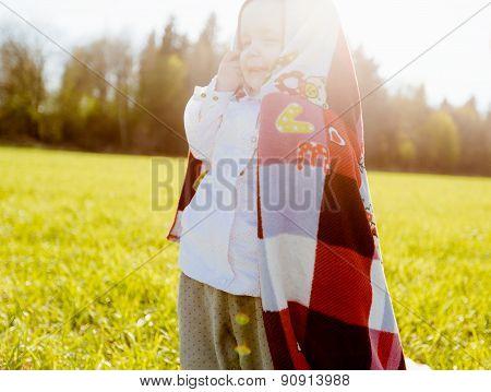 Little happy girl covered herself blanket