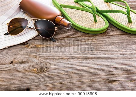 Beach accessories. Summer shoes and hat with sunglasses and suntan lotion on a wooden background