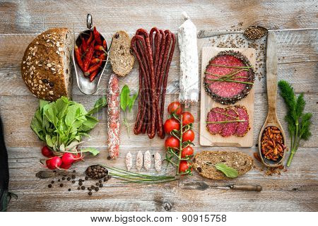 Wholemeal bread with dried salami  and vegetables on a wooden rustic table