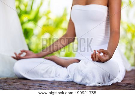 female practicing yoga outside in lotus position