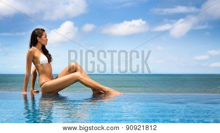 Beautiful woman in bikini sunbathing at the seaside, tropical resort