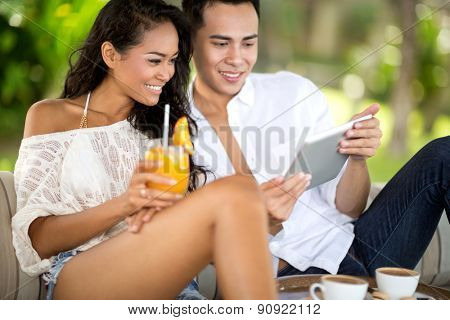 Handsome young couple in beach bar using digital tablet