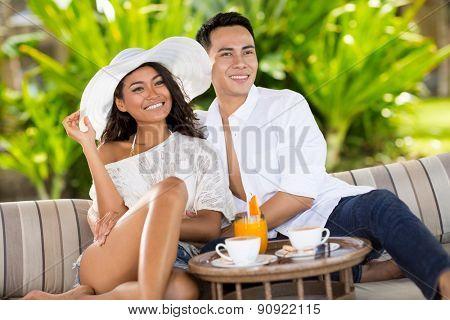 Smiling couple in tropical resort enjoying in drinks