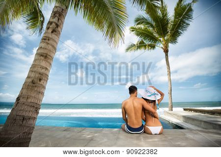 Beach vacation couple on summer holidays. Young happy Asian couple sitting on the rim of the swimming pool with the sea in the background