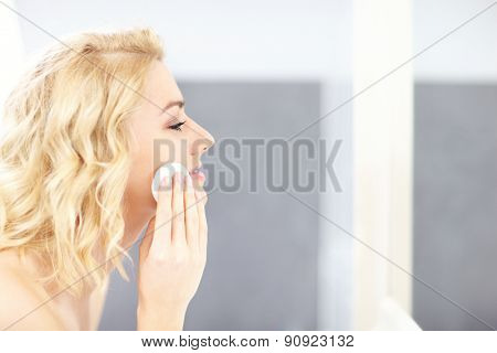 A picture of a woman cleaning face in the bathroom