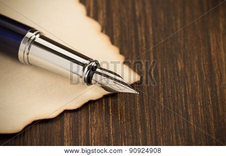 ink pen and paper parchment on wooden background