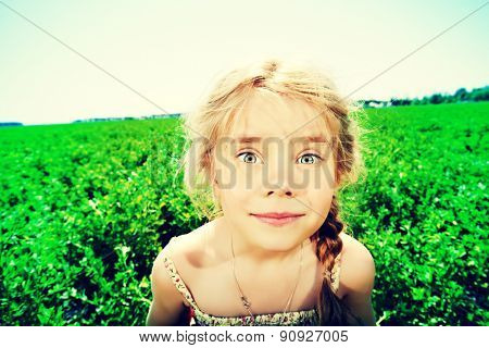 Portrait of a sly little girl in the countryside. Happy childhood. Emotions.