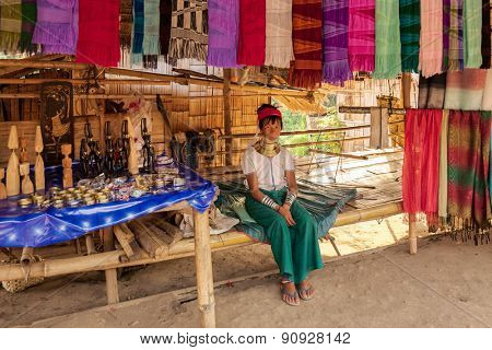 Chiang Mai, Thailand - April 24, 2009: A  lady waits for customer at her stall selling traditionally woven scarfs. The Karen tribe ladies are known to wear brass neck rings to extend the neck.