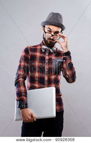Charismatic guy with ntebooki in glasses and plaid shirt