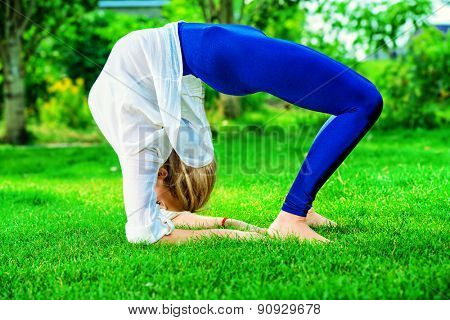 Beautiful young woman doing yoga stretching exercise in the summer park. Healthy lifestyle. Yoga.