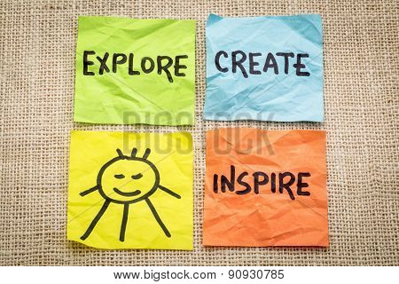 explore, create, inspire and smile reminder on sticky notes against burlap canvas