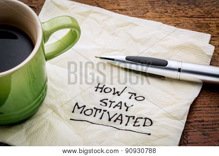 How to stay motivated - handwriting on a napkin with a cup of espresso coffee
