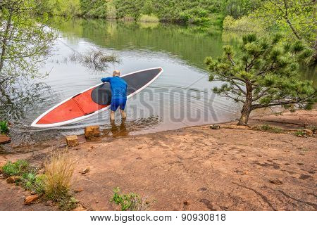 senior paddler launching  red SUP paddleboard on a rocky shore of a lake - Horsetooth Reservoir, Fort Collins, Colorado