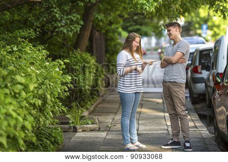 Young guy and girl jokingly talking on the street.