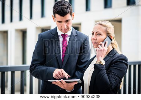 Business man and woman working outdoors with tablet computer in front of office building