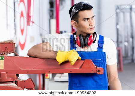 Asian carpenter with electric saw in workshop standing on a machine