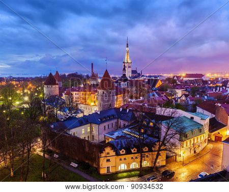 Aerial view of Tallinn Medieval Old Town with St. Olafâ??s Church and Tallinn City Wall illuminated in evening with dramatic cloudscape, Estonia