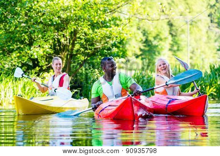 Friends paddling with canoe on forest river