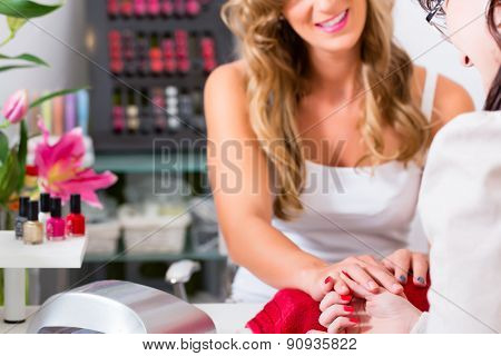Woman receiving manicure in beauty parlor, her nails being polished