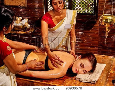 Young woman having oil Ayurveda spa treatment. Two masseuses.