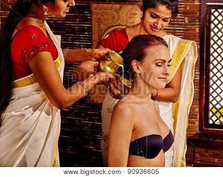 Young sitting woman having ayurveda spa treatment.