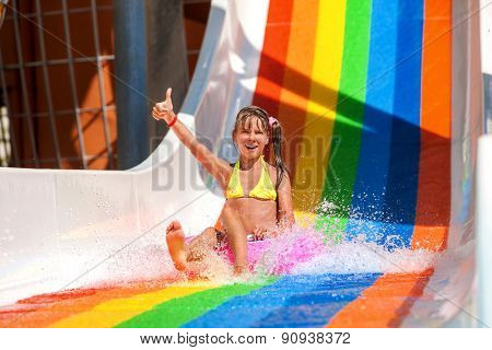 Happy child girl in yellow bikini sliding water park and show thumb up.