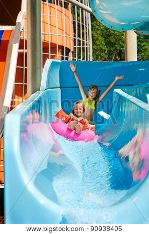 Children  with hands up on water slide at aquapark. Summer holiday.