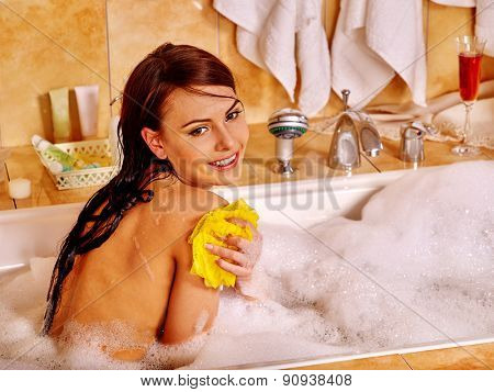 Young woman take bubble  bath. Home interior.