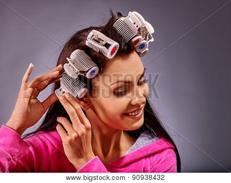 Happy woman wear hair curlers on head. Gray background.