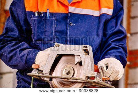 Hands of man  builder holding circular saw.