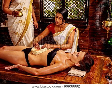Young woman having stomach massage oil Ayurveda spa treatment.