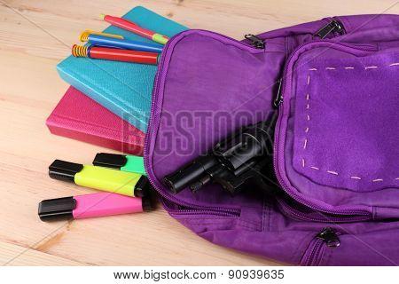 Gun in school backpack on wooden background