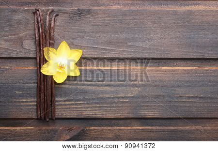 Vanilla pods and orchid flower on wooden background