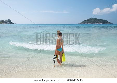 Preteen child on a tropical beach with snorkeling equipment