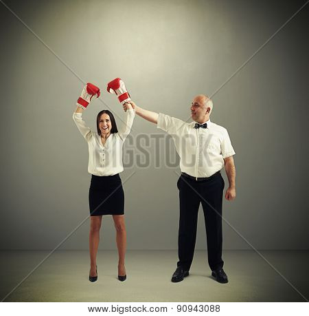referee holding winner businesswoman in boxer gloves and looking at her over dark grey background