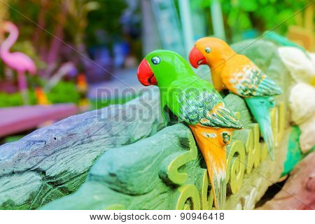 Parrots orange and green statue in garden made with pastel.