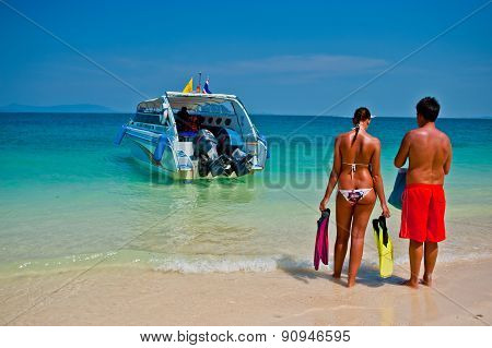 Tourists stand waiting speed boat on the beach in Phuket. Thailand