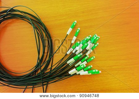 A group head connector fiber optic green color on brown table made with vintage color.Fiber Optics c