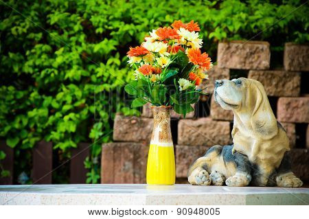 Flower and dog statues on wall background.
