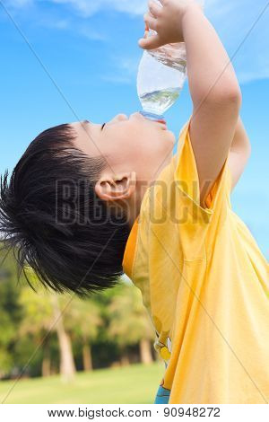 Little Asian Boy Drinking Water From Plastic Bottle