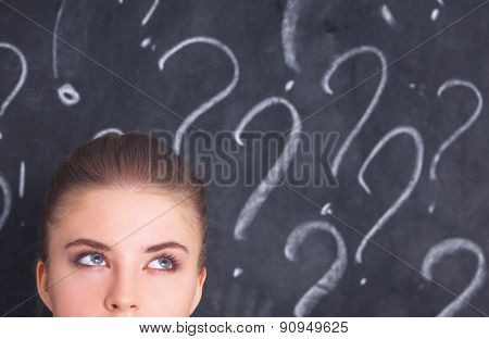 Young girl with question mark on a gray background .