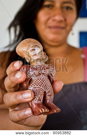 Unidentified woman holding ceramic figurine in Agua Blanca Museum, Machalilla National Park, Ecuador