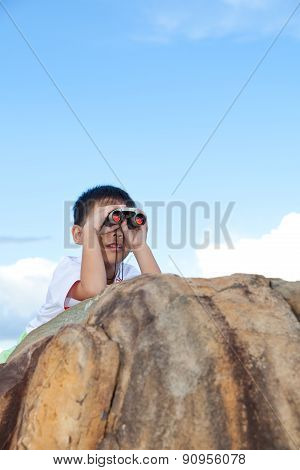 Happy Little Boy Exploring Outdoors Clambering On A Rock With Telescope