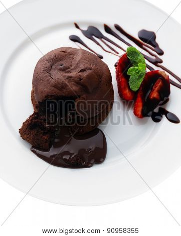 Chocolate fondant with strawberries on white plate, closeup