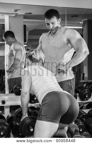 Man and woman trained in the gym. Trainer demonstrates exercises, girl.