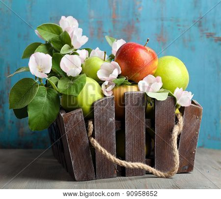 Fresh apples with apple blossom in crate, on wooden table