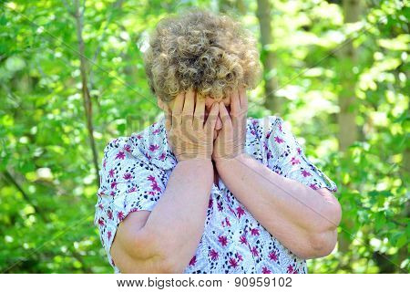 Mature Woman Covering Her Face With  Hands In Sorrow