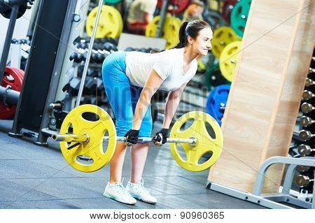 fitness woman doing exercises for back muscles with heavy weight