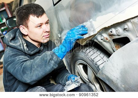 auto mechanic worker plastering body car at automobile repair and renew service station shop before painting restoration