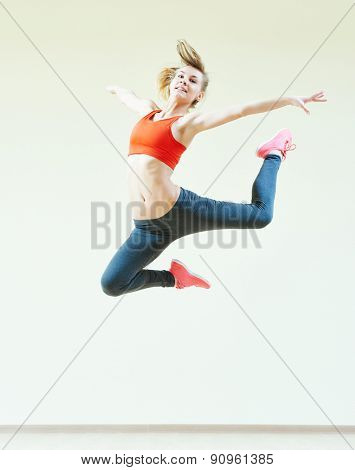 fitness instructor jumping during aerobics dancing exercises in sport club